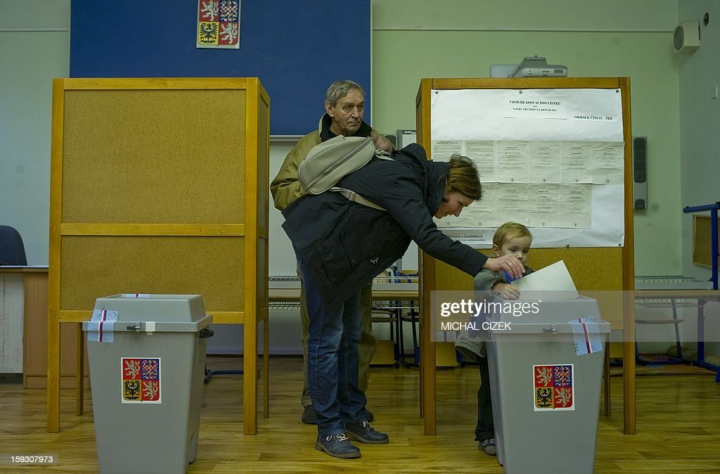 A mother helps her son to cast her ballot at a polling station in Prague on January 11, 2013. Czech polling stations opened on January 11 afternoon in local mid-time for the first round of the first Czech direct presidential election in history.