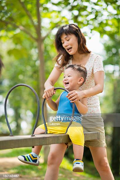Mother helps little boy to play seesaw