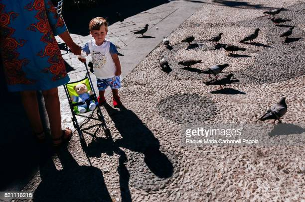 BARRAMEDA CADIZ ANDALUCíA SPAIN A mother her baby and a teddy on baby stroller standing next to pigeons