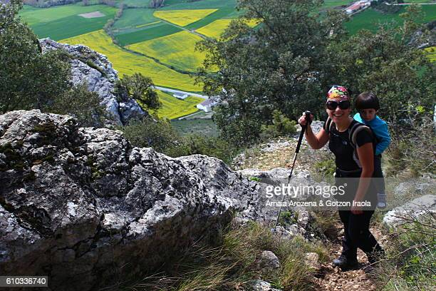 Mother hiking and carrying her little daughter in backpack in Lokiz mountain range, Navarre