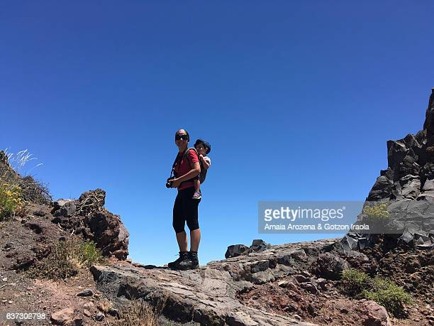 Mother hiking and carrying her little daughter in backpack in Roque de los Muchachos. La Palma island, Canary islands, Spain