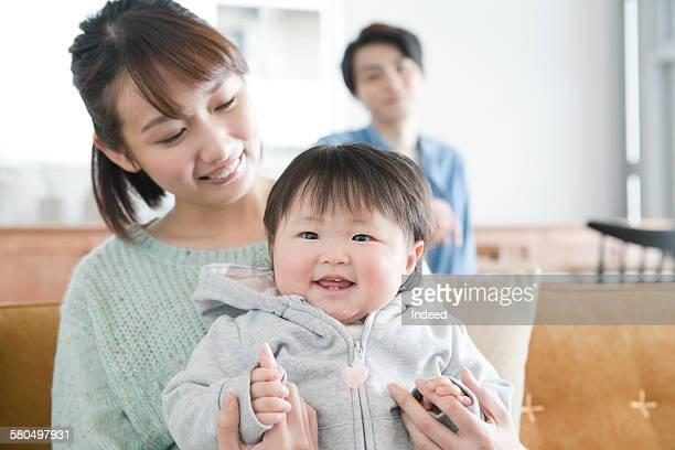 Mother hodling baby girl on sofa