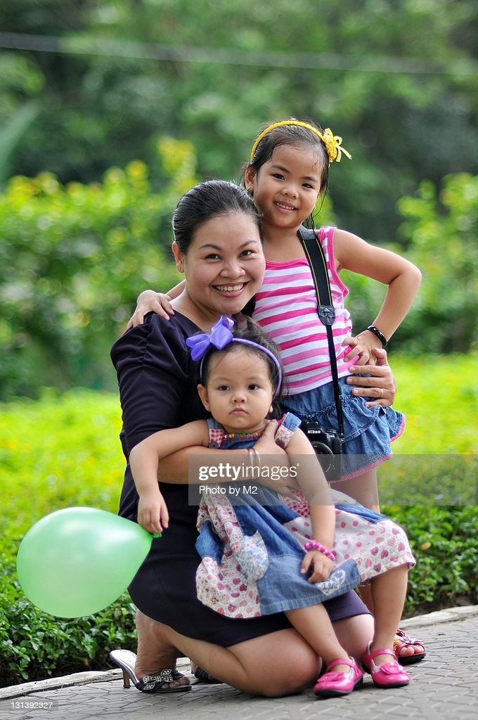 Mother holding 2 daughters in park under sunlight
