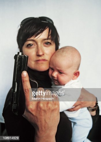 A Mother Holding A Handgun Up And A Baby In Her Other Arm ...