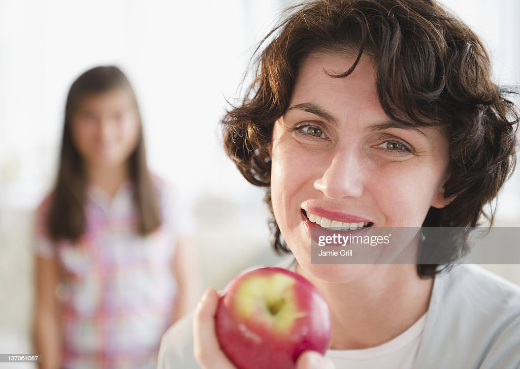 Mother holding apple, daughter in background : Stock Photo