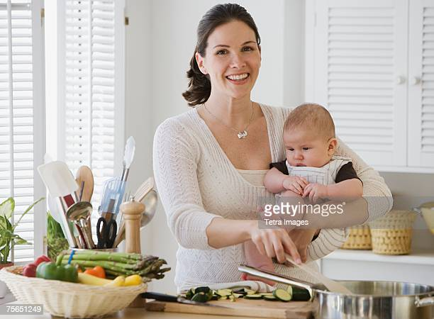 Mother holding baby and cooking