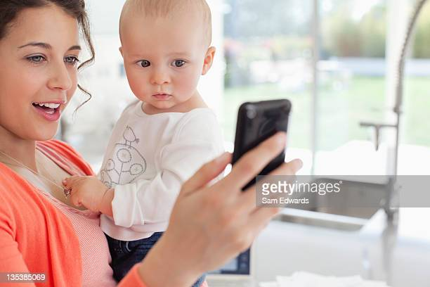 Mother holding baby and using cell phone