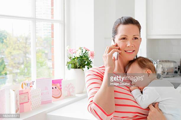 Mother holding baby and using cellphone