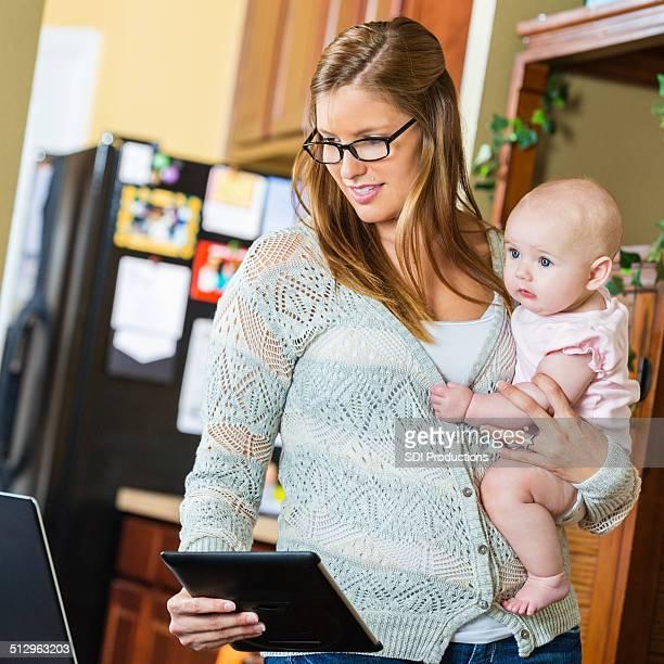 Mère tenant bébé et à l'aide de tablette numérique dans bureau à domicile