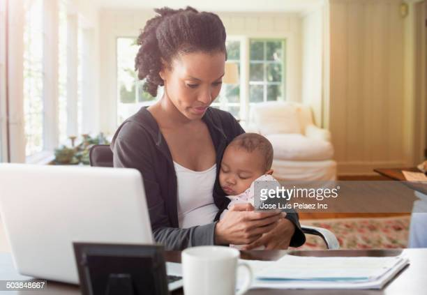 Mother holding baby and working in living room