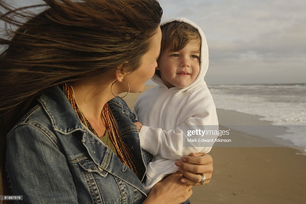 Mother holding baby at beach : Stock Photo