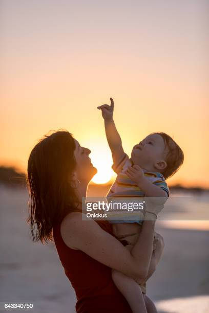Mother Holding Baby Boy at Beach Sunset