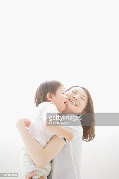 Mother holding Baby Boy in arms, smiling