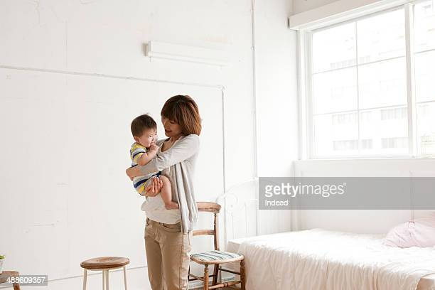 Mother holding baby boy in room