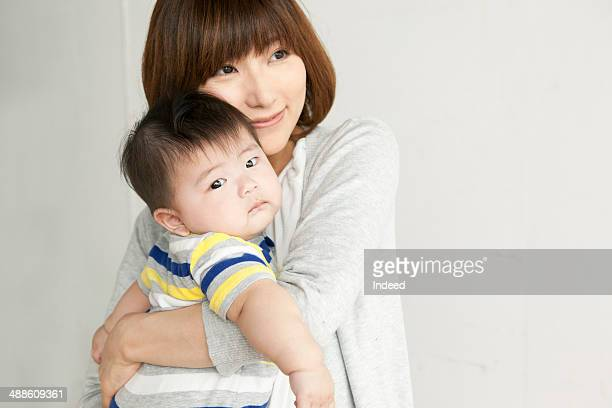 Mother holding baby boy, looking away