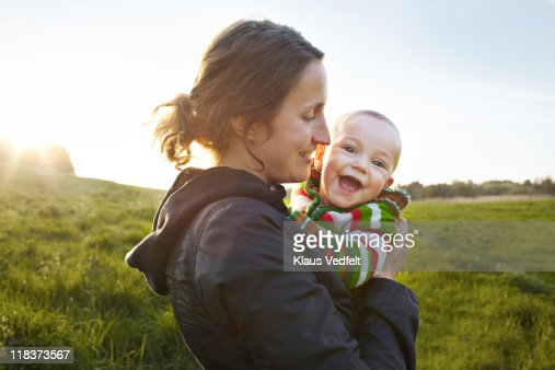 Mother holding baby boy smiling to camera : Stock Photo
