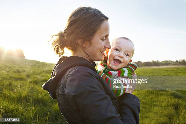 Mother holding baby boy smiling to camera