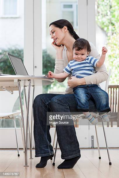 Mother holding baby boy, using cellphone and laptop
