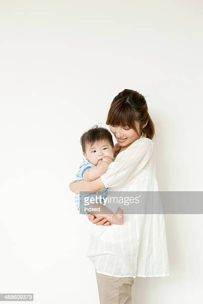 Mother holding baby by wall