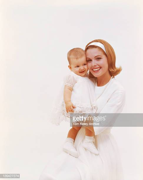 Mother holding baby daughter against white background