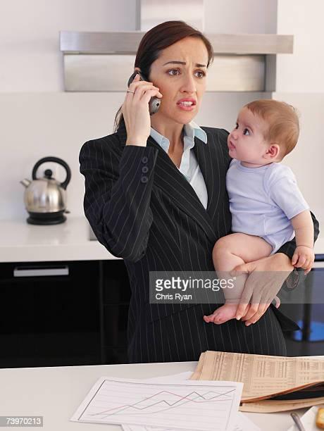 Madre sostiene hija bebé mientras hablando por teléfono en la cocina