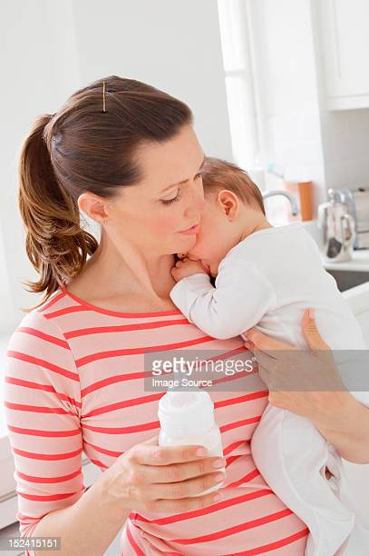 Mother holding baby girl and bottle