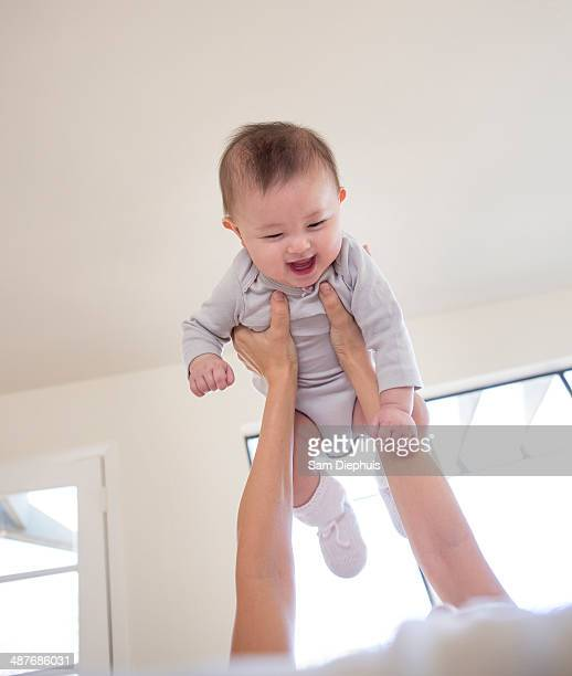 Mother holding baby girl overhead
