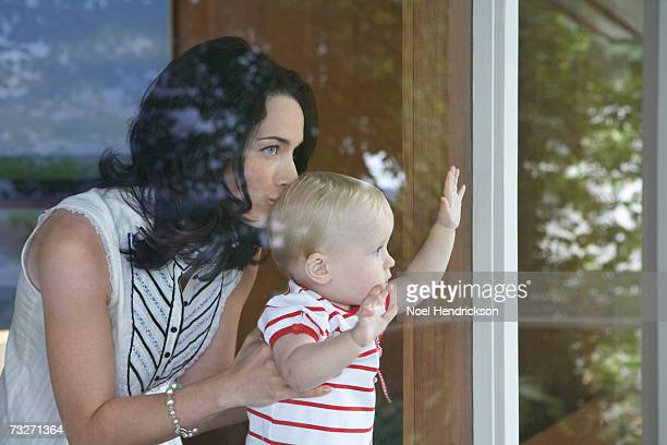 Mutter holding baby Mädchen (9-12 Monate), Fenster