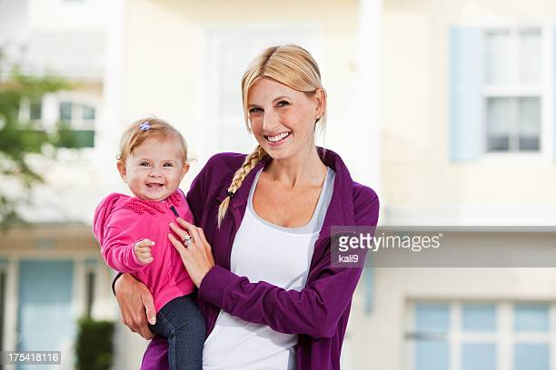 Mother holding baby in front of house