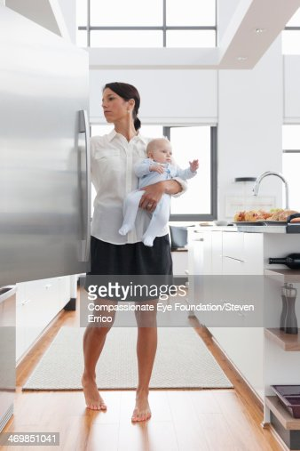 Mother holding baby in kitchen opening fridge : Stock Photo