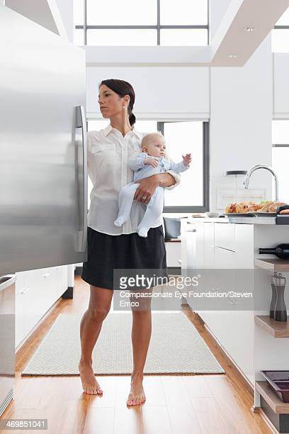 Mother holding baby in kitchen opening fridge