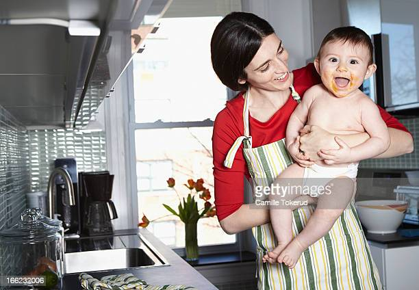 Mother holding baby in kitchen smiling