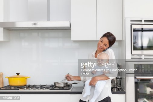 Mother holding baby in kitchen using mobile phone