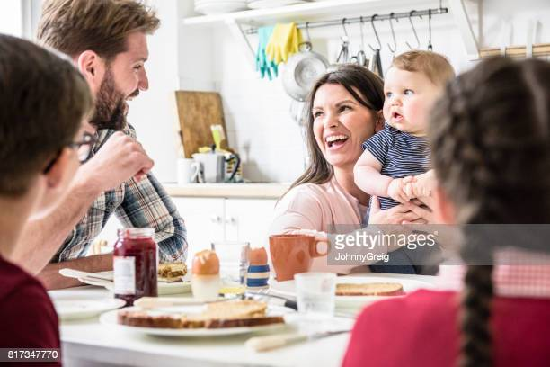 Mother holding baby looking at mid adult man and laughing, older children sitting at table