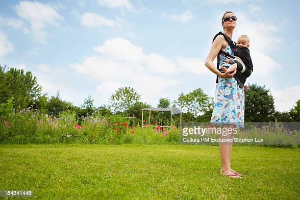 Mother holding baby on green lawn