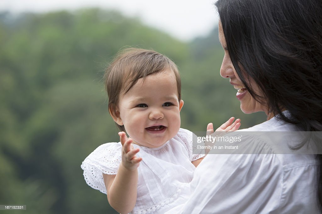 Mother holding  baby outdoors : Stock Photo