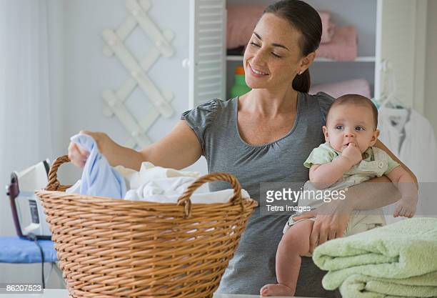 Mother holding baby son and sorting laundry