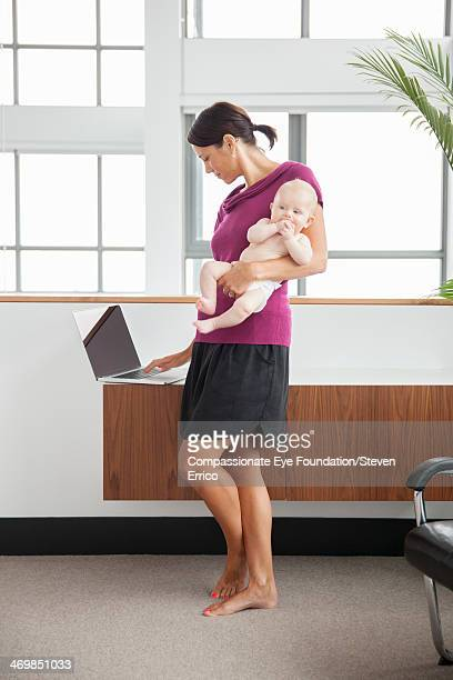 Mother holding baby son using laptop