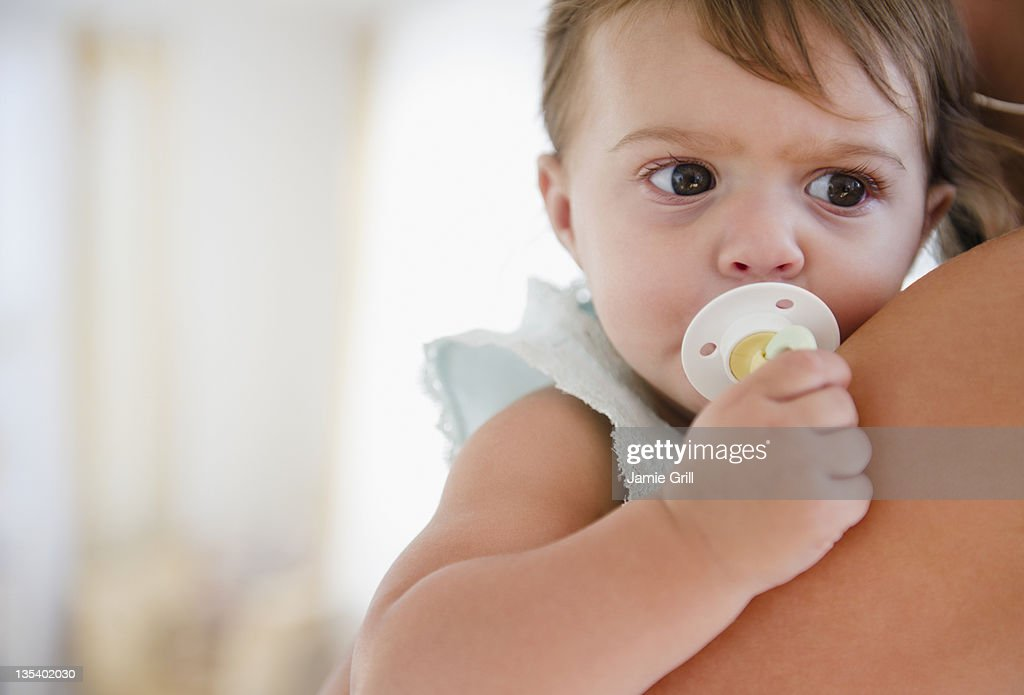 Mother holding baby with pacifier : Stock Photo