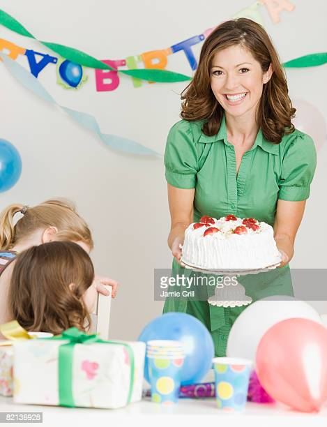 Mother holding birthday cake at party