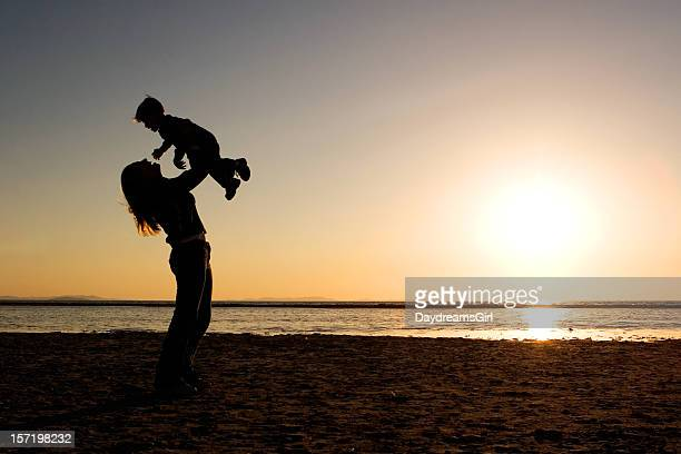 Mother holding child high up against rising sun at the beach