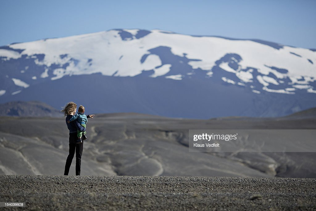 Mother holding child pointing at mountain : Stock Photo
