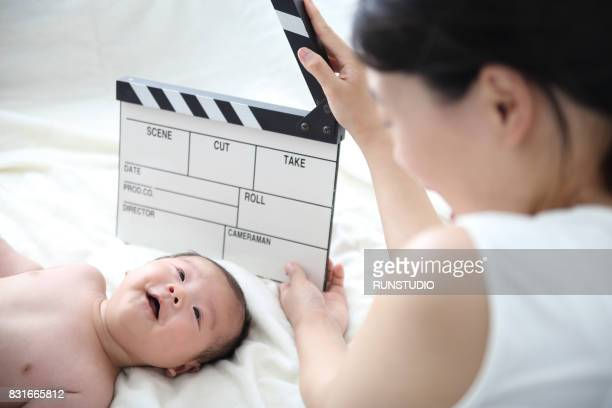 mother holding clapper board and baby smiling