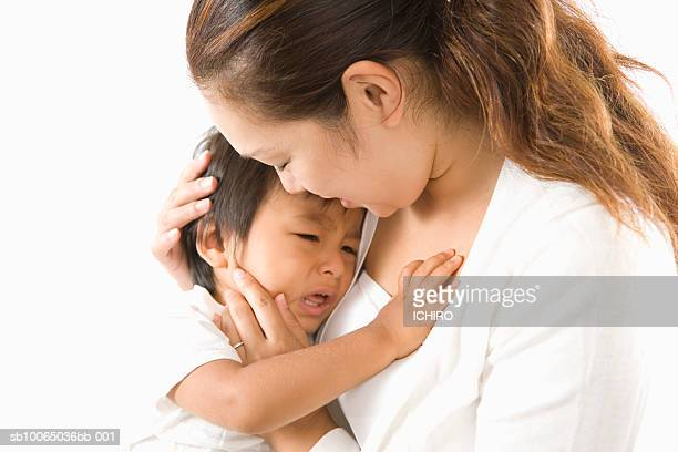 Mother holding crying son (6-9 months) against white background