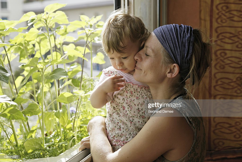 Mother holding daughter at home : Stock Photo