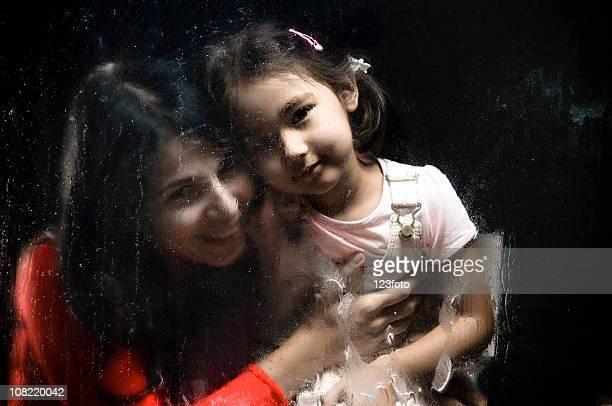 Madre tenendo la figlia dietro a umido e piovoso finestra