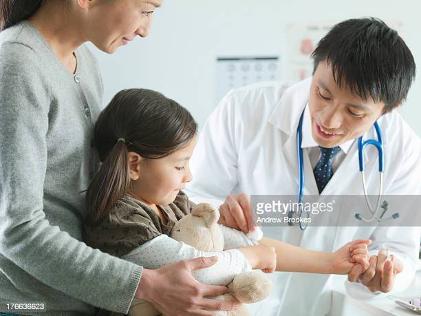 Mother holding daughter being examined by paediatrician