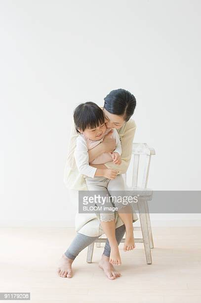 Mother holding daughter in arms