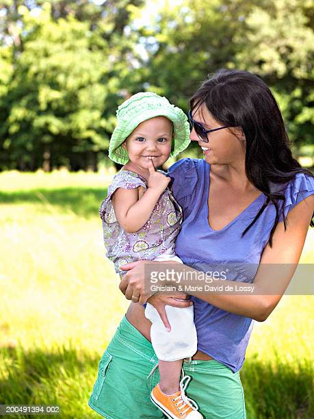 Mother holding daughter (18-21 months) in field, smiling