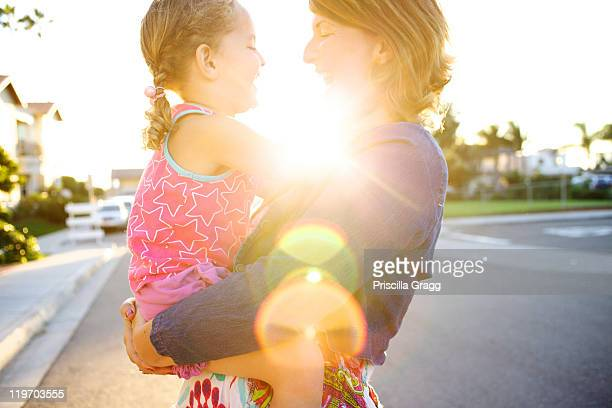 Mother holding daughter in street